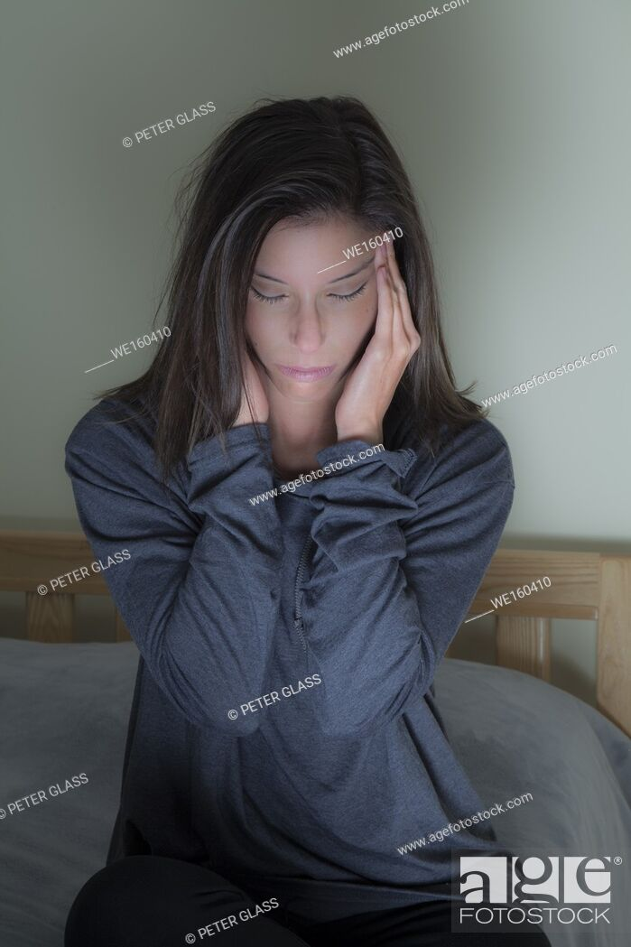 Photo de stock: Young woman sitting on her bed, hands on her head.