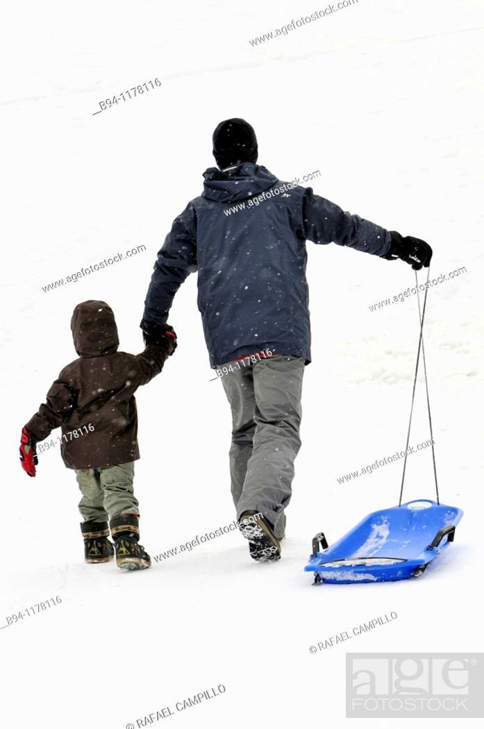 Stock Photo: Man and boy with plastic sled. La Molina ski resort, Cerdanya, Girona province, Catalonia, Spain.