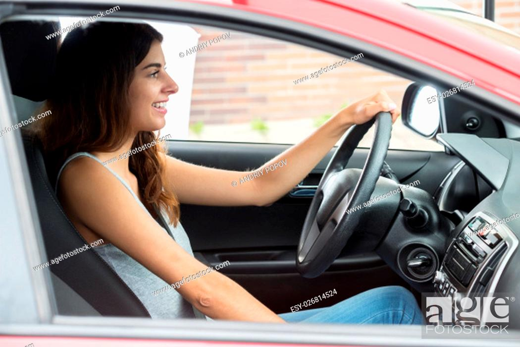 Stock Photo: Side View Of Young Happy Woman Sitting Inside Car.