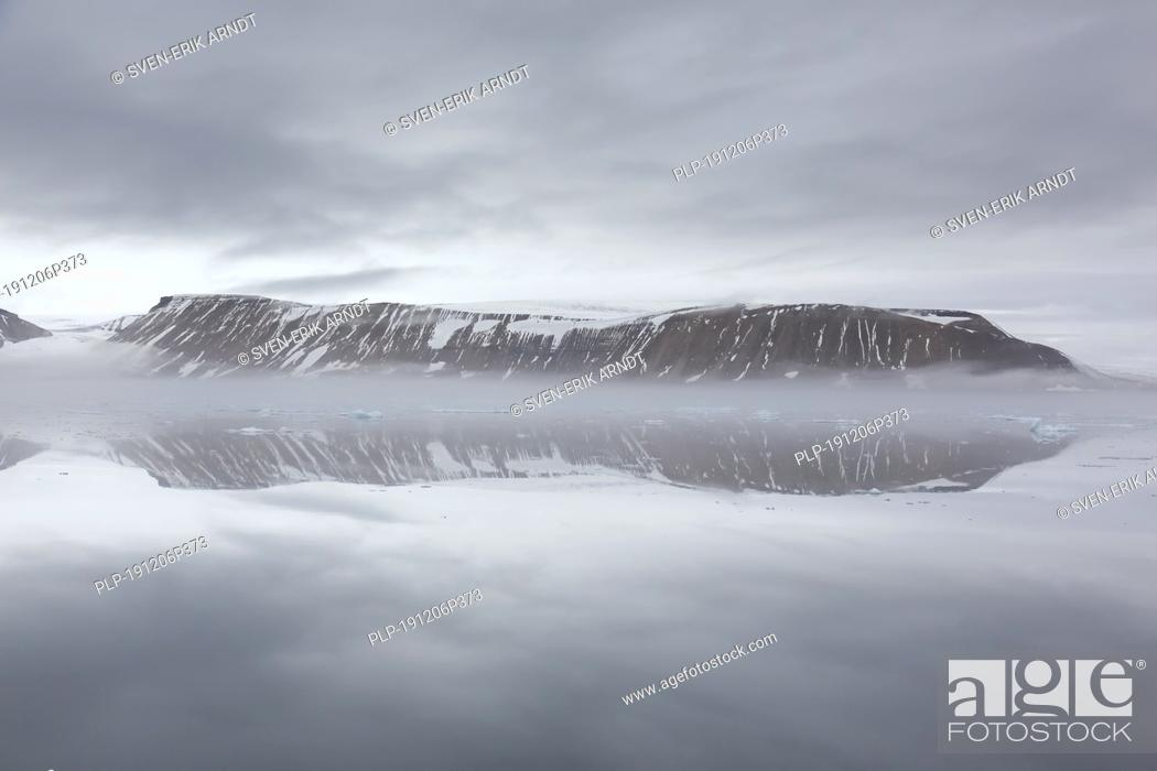 Stock Photo: Mountains in the fog along the coast at Hinlopenstretet / Hinlopenstreet / Hinlopen strait between Spitsbergen and Nordaustlandet in Svalbard, Norway.