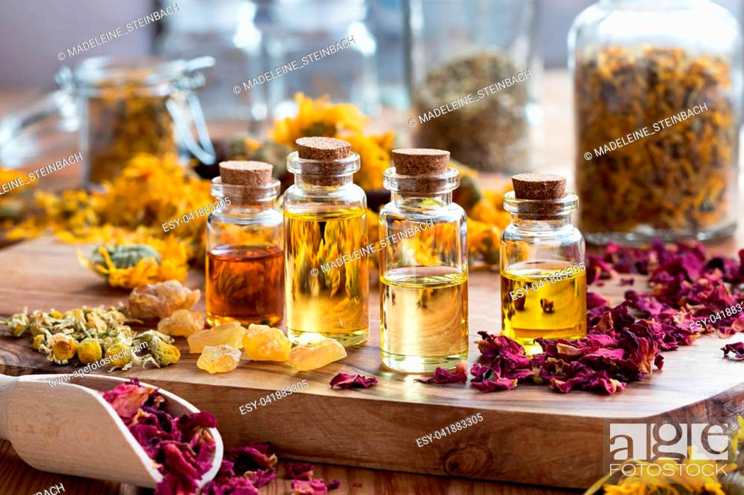 Stock Photo: Bottles of essential oil with dried rose petals, chamomile, calendula and frankincense resin on a wooden table.