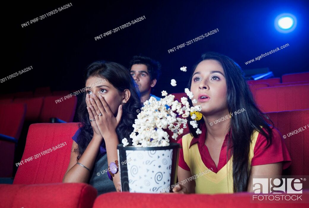 Imagen: Two female friends looking surprised while watching movie in a cinema hall.