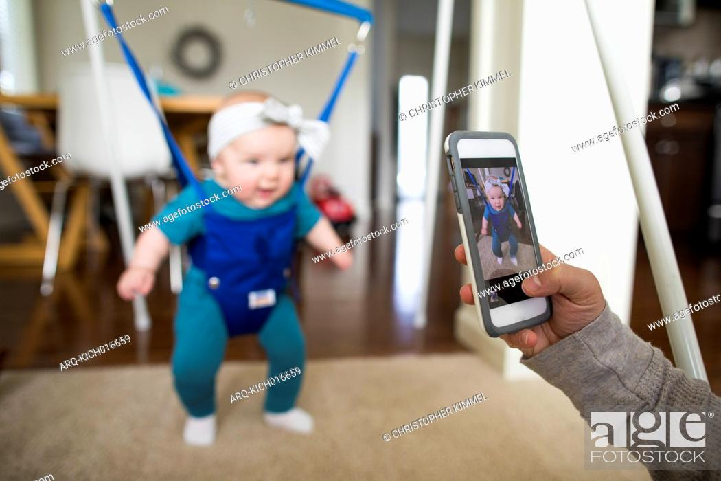 Stock Photo: Parent photographing baby in baby bouncer with smartphone at home.