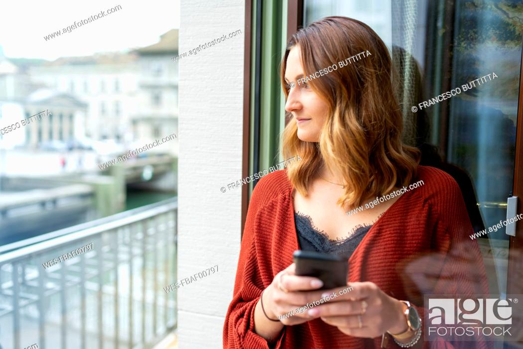 Stock Photo: Young woman using cell phone at the balcony door.