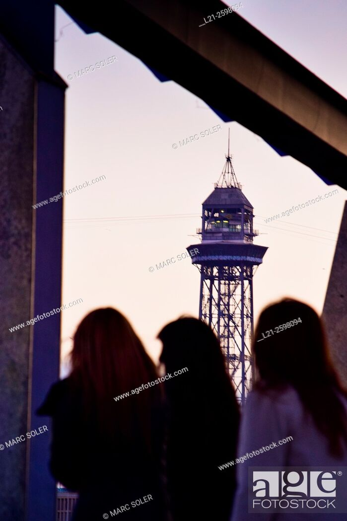 Stock Photo: Cable car tower at dusk. Silhouette of three women back. Barcelona, Catalonia, Spain.