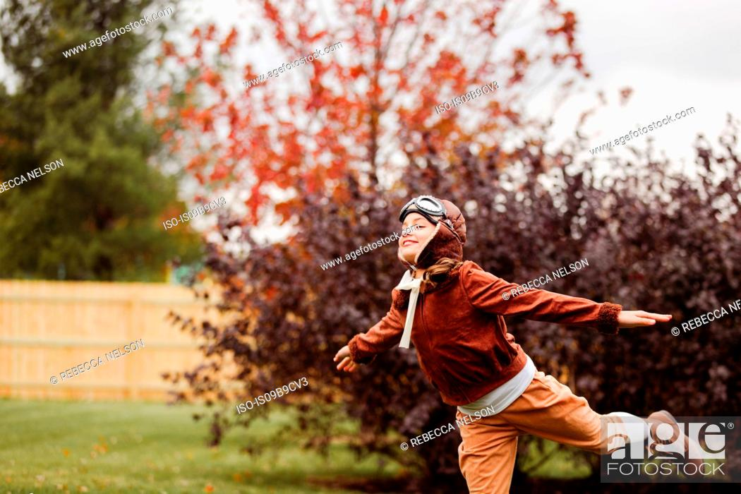 Photo de stock: Girl wearing pilot costume for halloween with arms open in park.