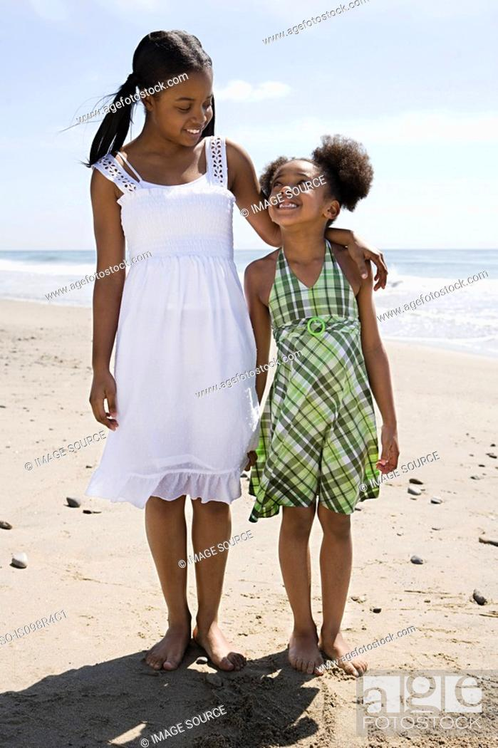 Stock Photo: Sisters standing on a beach.