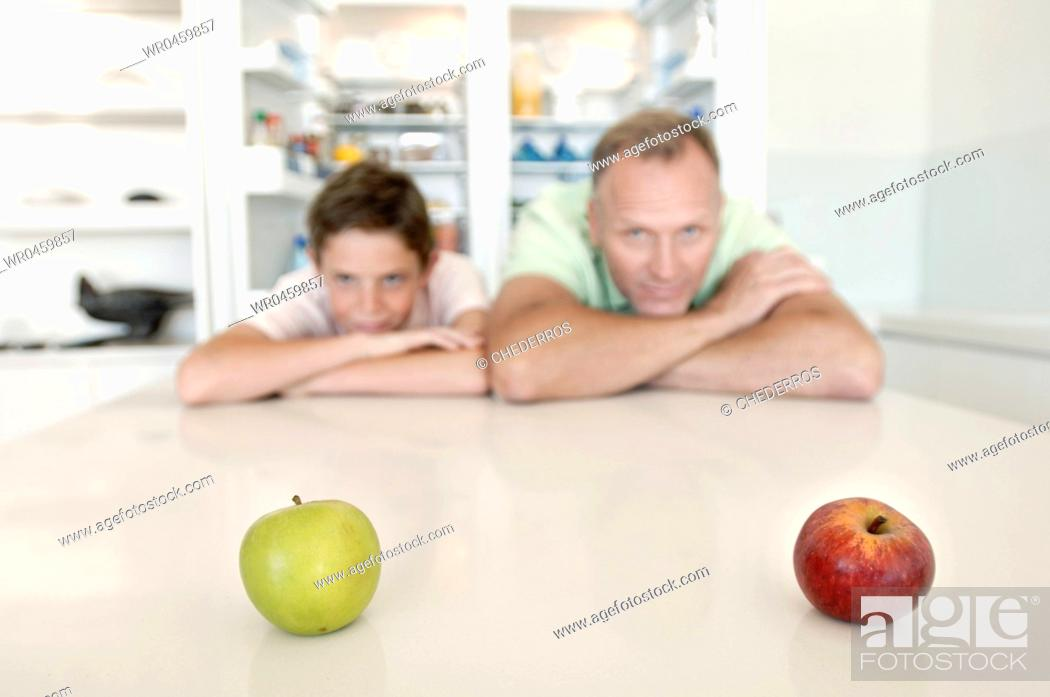 Imagen: Mature man and his son leaning over a table and looking at apples.