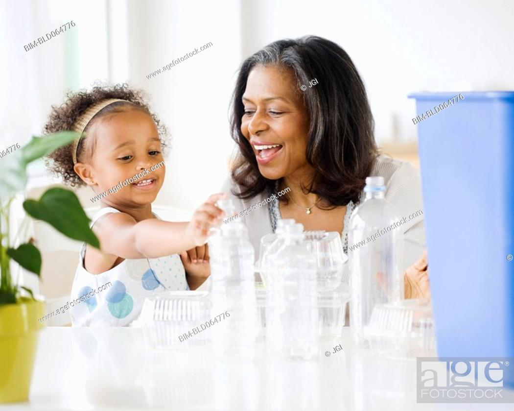 Stock Photo: African grandmother teaching granddaughter how to recycle.