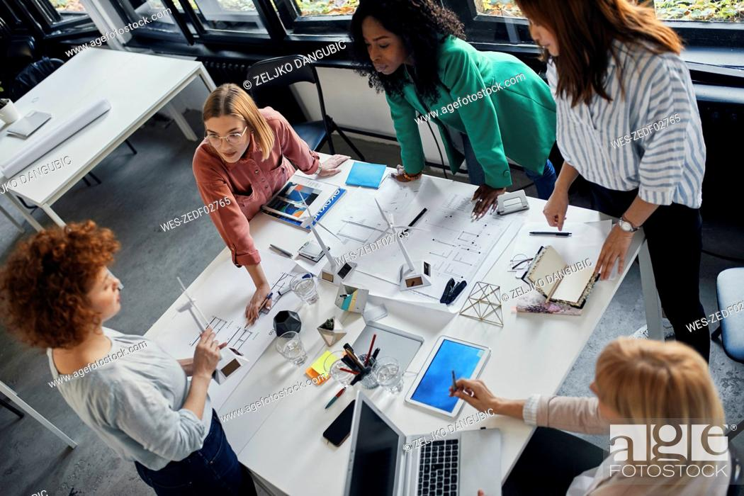 Stock Photo: Businesswomen having a meeting in office with wind turbine models on table.