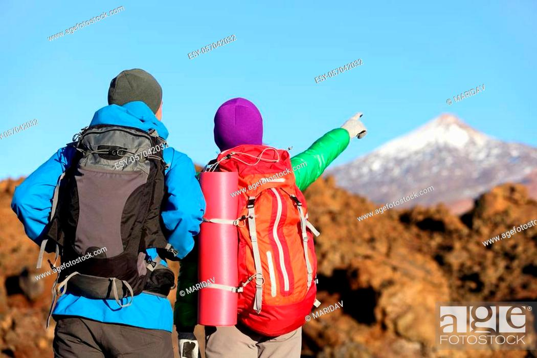 Stock Photo: Hikers looking at view pointing hiking in mountain. People hiker couple in nature landscape trekking wearing backpacks. Woman and man on volcano Teide, Tenerife.