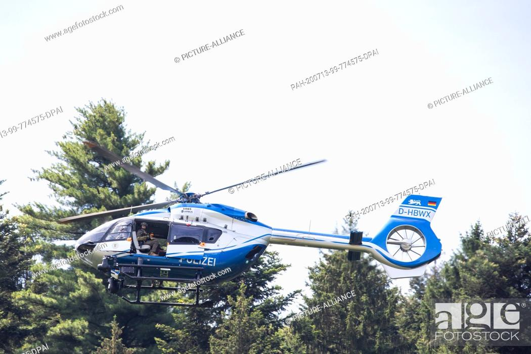 Stock Photo: 13 July 2020, Baden-Wuerttemberg, Oppenau: A police helicopter flies over the forest near the community of Oppenau. Because of the police operation in Oppenau.