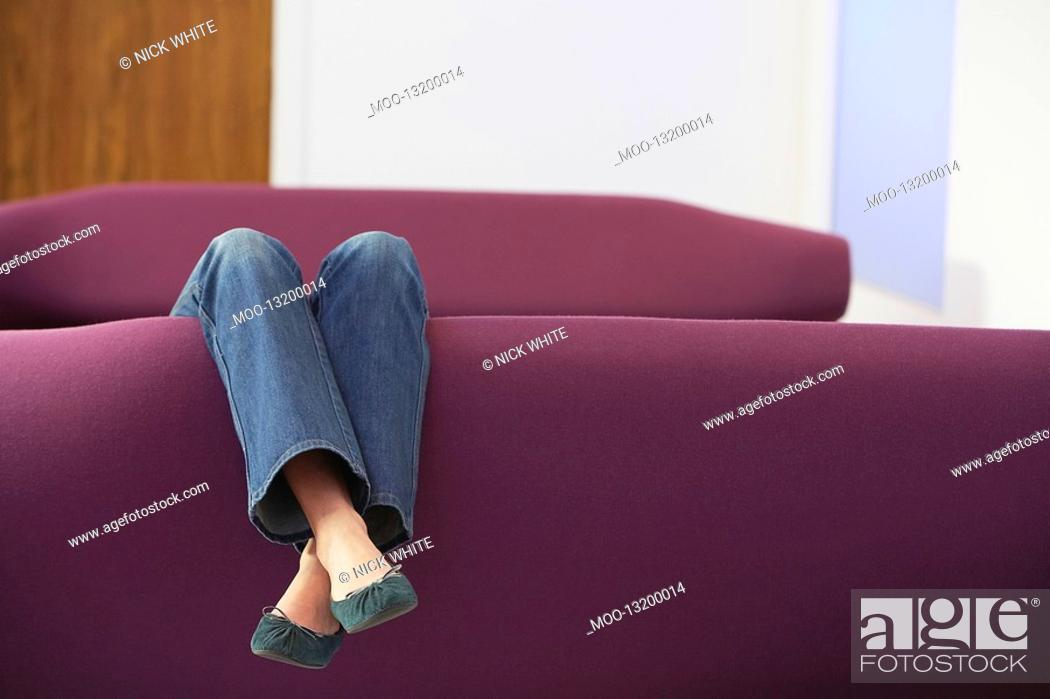 Stock Photo: Woman Relaxing upside down on Sofa low section.