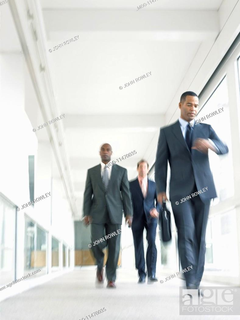 Stock Photo: Businessmen walking down corridor low angle view.