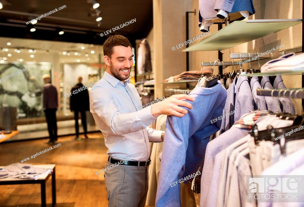 Stock Photo: sale, shopping, fashion, style and people concept - happy young man in shirt choosing jacket in mall or clothing store.