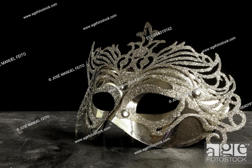 Stock Photo: silvery carnival mask on dark and black background.