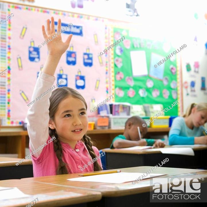 Stock Photo: Girl raising hand in classroom.