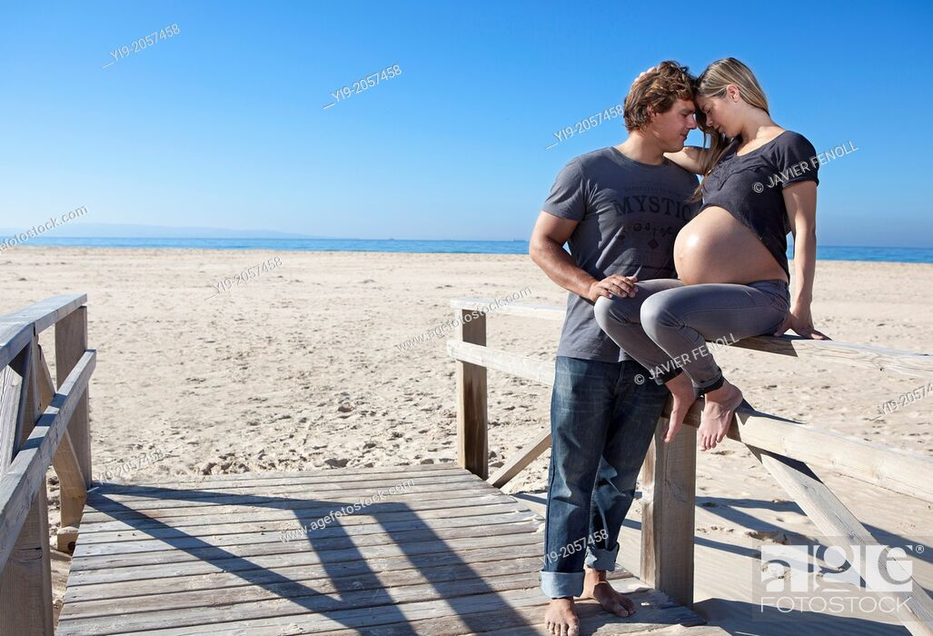 Stock Photo: A pregnant woman and her partner on the beach.