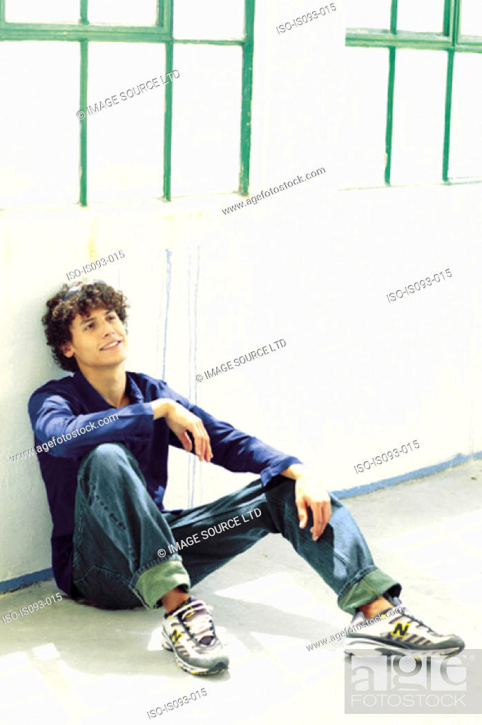 Stock Photo: Man sitting against wall.