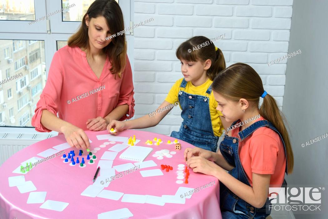 Stock Photo: Mom and two daughters play board games.