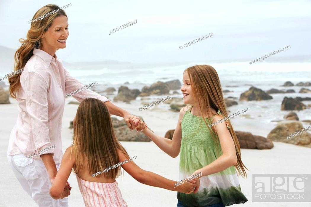 Stock Photo: Mother playing with two daughters 7-9 10-12 on beach.