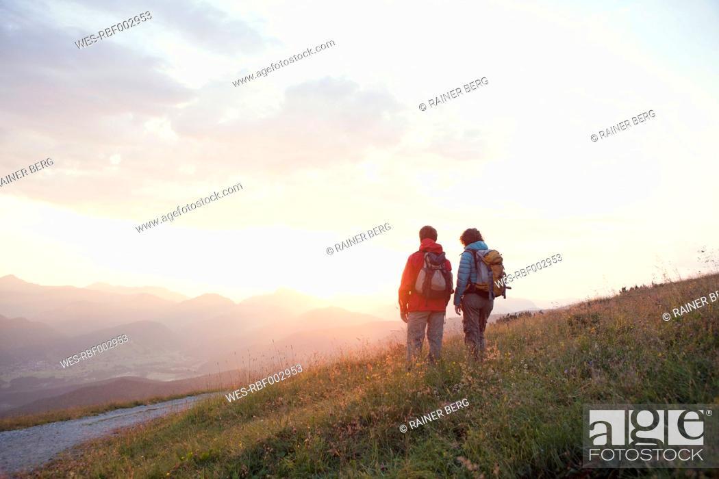 Photo de stock: Austria, Tyrol, couple hiking at Unterberghorn at sunrise.