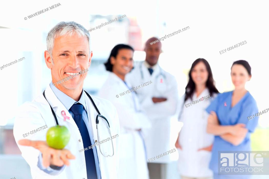 Stock Photo: Composite image of mature doctor holding an apple.