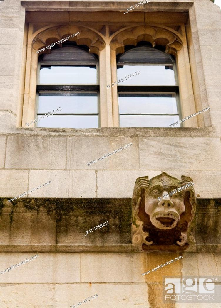 Stock Photo: A surprised looking gargoyle on an Oxford College UK with the college window behind.