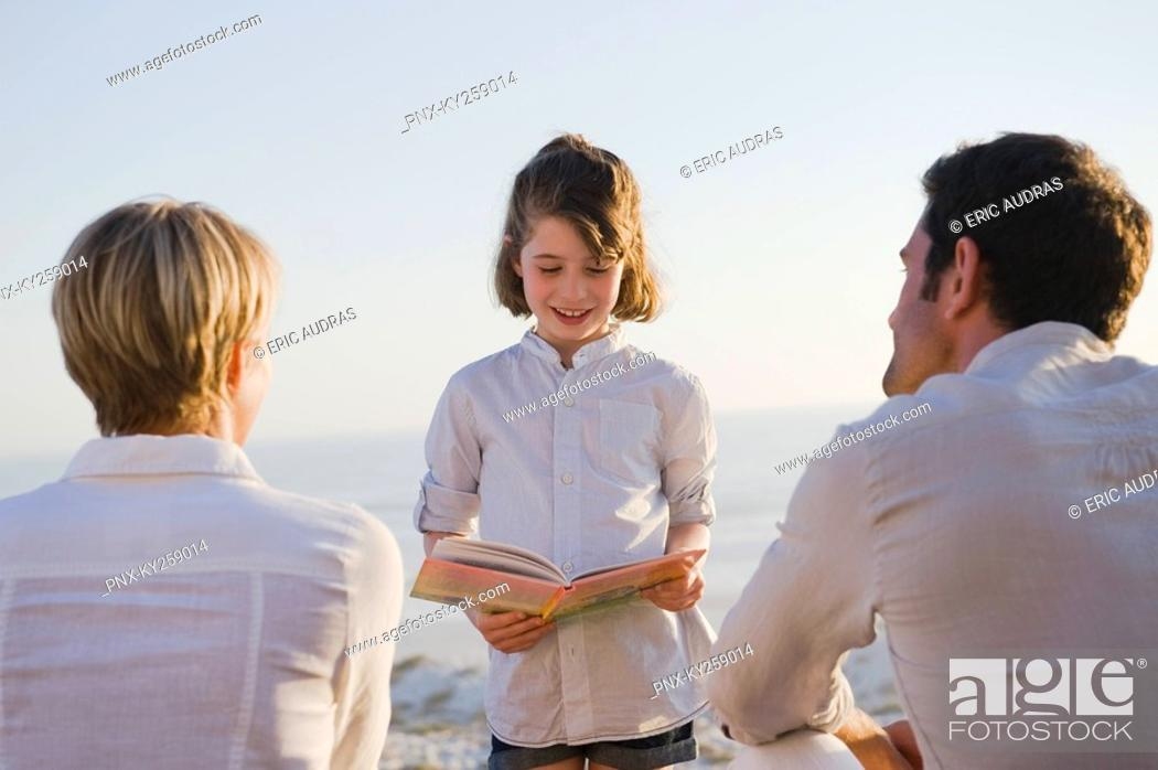 Stock Photo: Girl reading a book in front of her parents.
