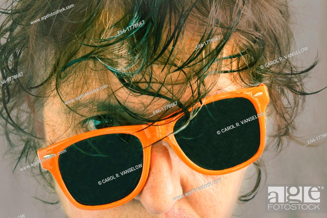 Stock Photo: portrait of woman with wet hair and tilted orange sunglasses Processed with InstaGram look with soft grey background.