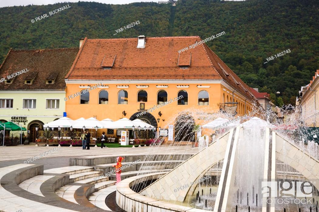 Stock Photo: Brasov Transylvania Romania Europe / Fountain in pedestrianised Council Square Piata Sfatului with pavement cafes in medieval city centre.