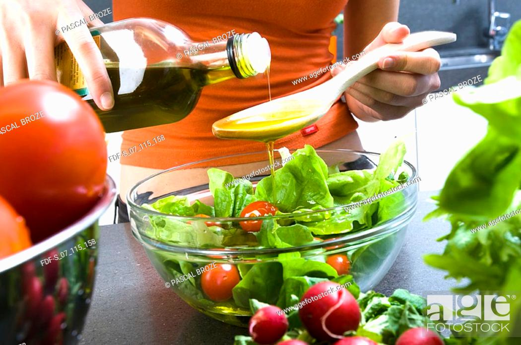 Stock Photo: Mid section view of a woman pouring olive oil into a wooden spoon.