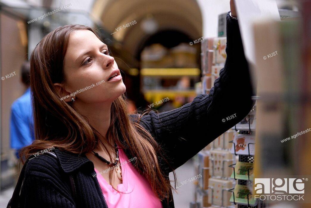 Imagen: junge Frau betrachtet Ansichtskartenstaender. - Austria, 25/07/2007.