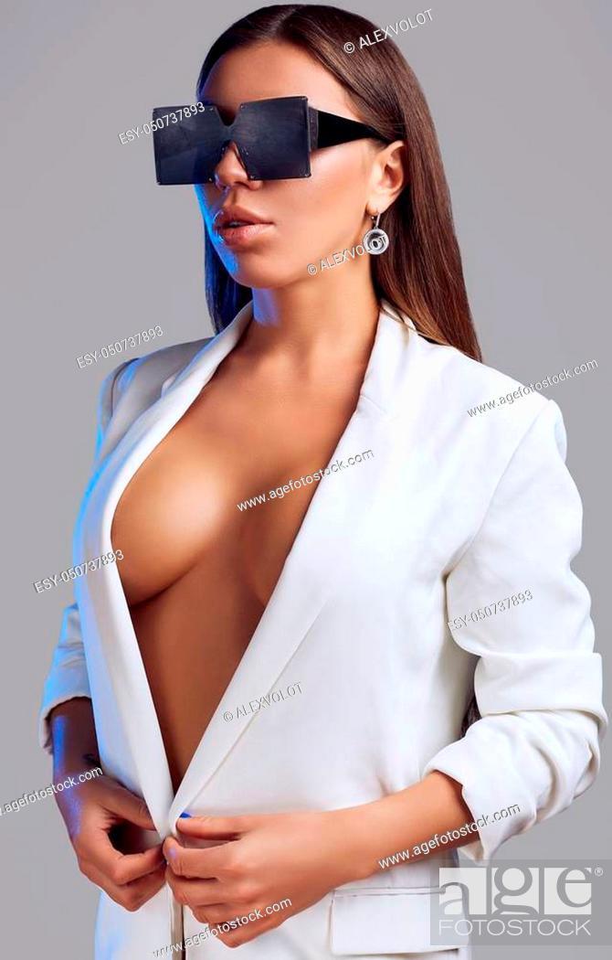 Stock Photo: Portrait of gorgeous beautiful brunette with fashion glasses wearing white jacket on gray background.