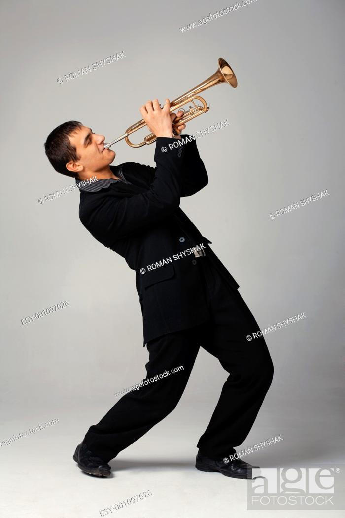 Stock Photo: Portrait of a young man playing his Trumpet.