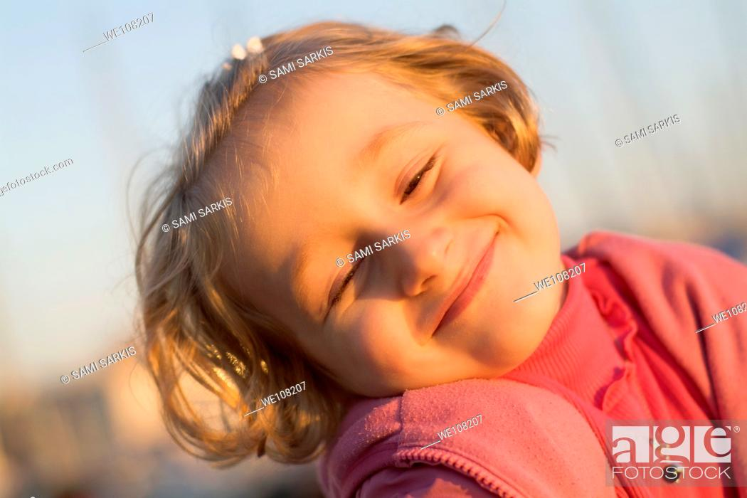 Stock Photo: Portrait of a smiling little girl at sunset, France.