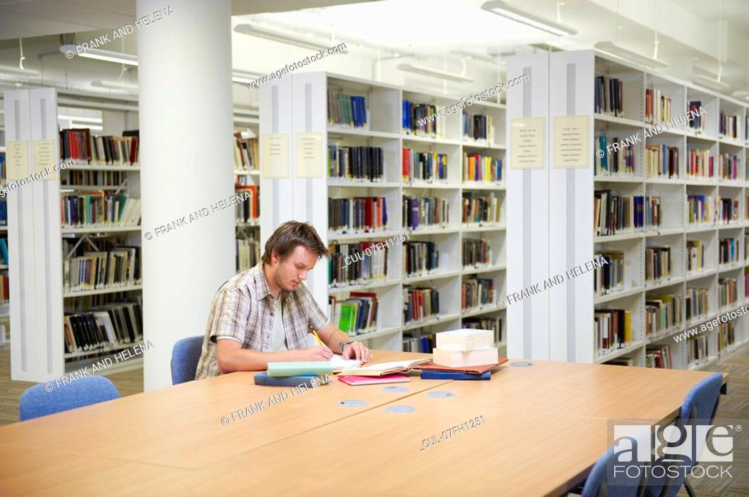 Stock Photo: Young man working in library.