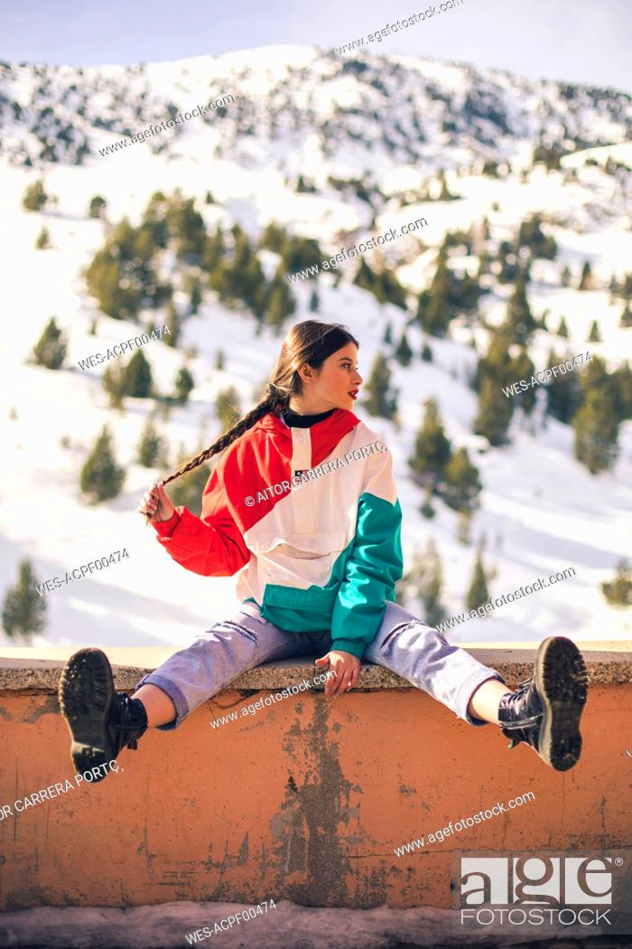 Stock Photo: Spain, Benasque, teenage girl sitting on a wall in winter.