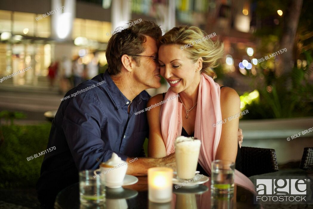 Imagen: Caucasian man kissing wife in restaurant.