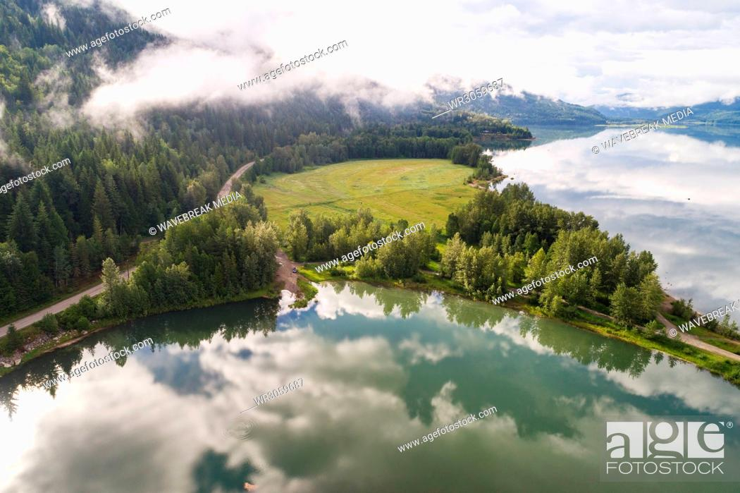 Stock Photo: Clouds reflecting in the river near the forest landscape.