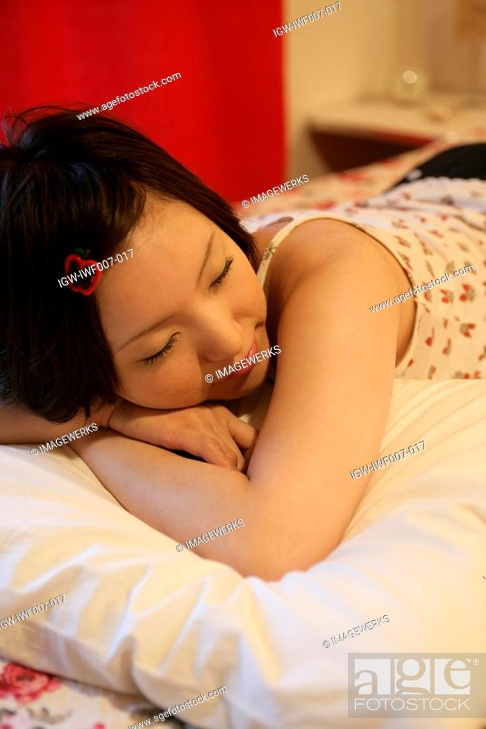 Stock Photo: A young woman sleeps peacefully on the bed in a cozy bedroom.