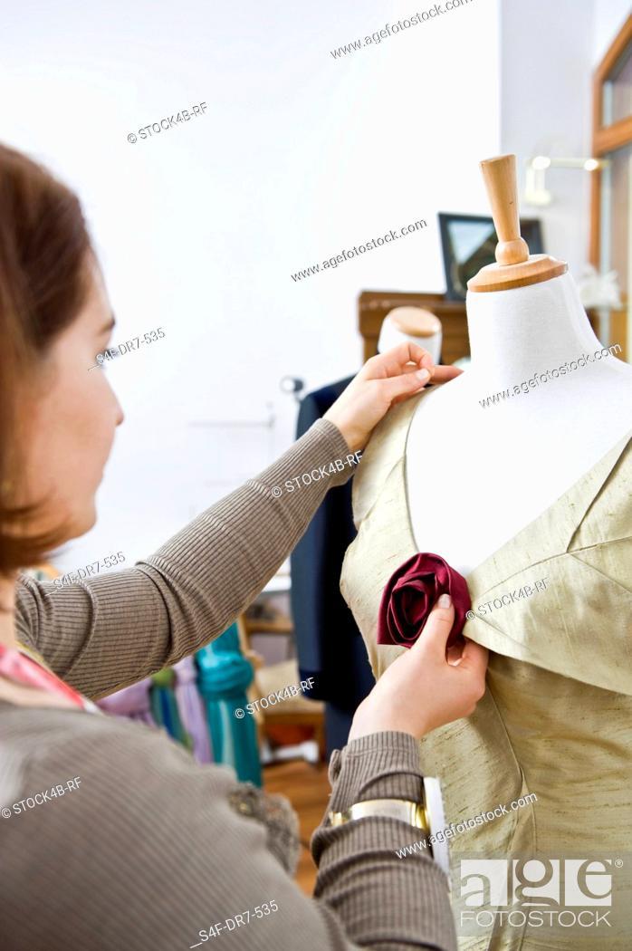 Stock Photo: Tailoress in studio at work.