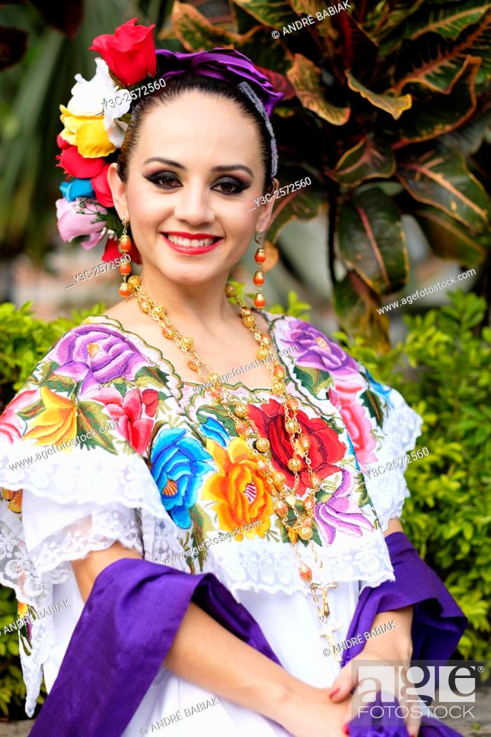 Stock Photo: Young hispanic woman smiling while wearing Mexican folklore outfit.
