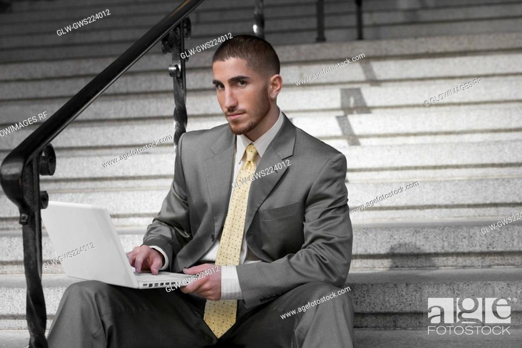 Stock Photo: Portrait of a businessman sitting on a staircase and using a laptop.