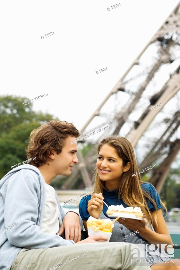 Stock Photo: Young couple eating fast-food with Eiffel tower in background, Paris, France.