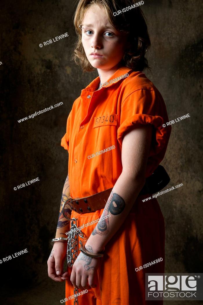 Imagen: Studio portrait of sad boy in handcuffs and chains.