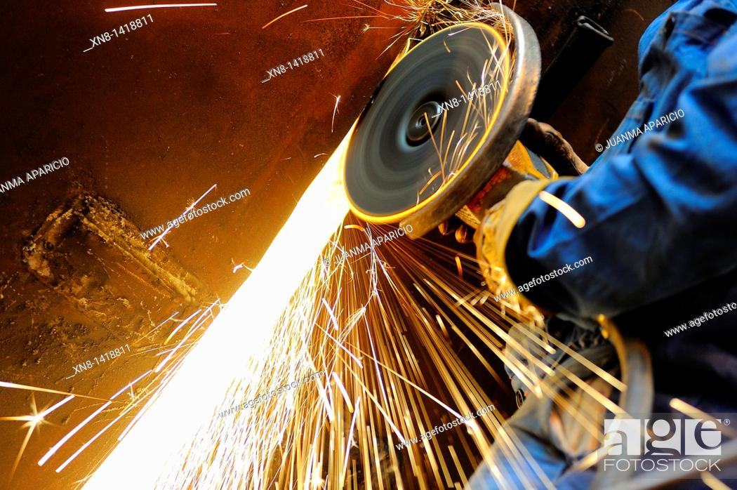 Stock Photo: Industrial grinding a piece worker in a short flat.