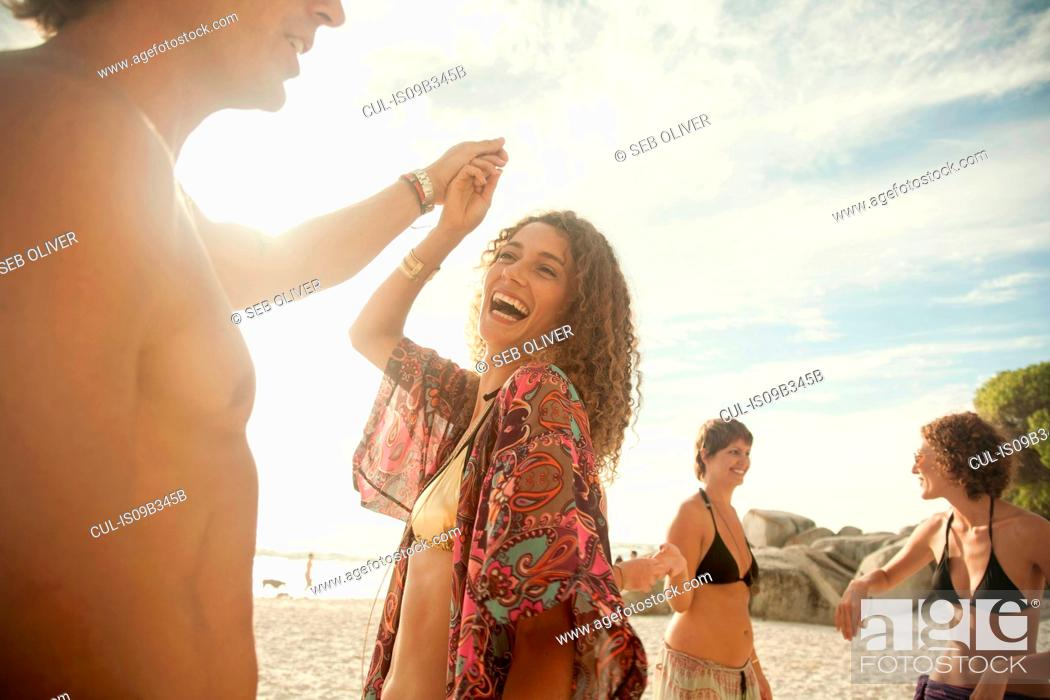Stock Photo: Group of friends at beach, fooling around, dancing.