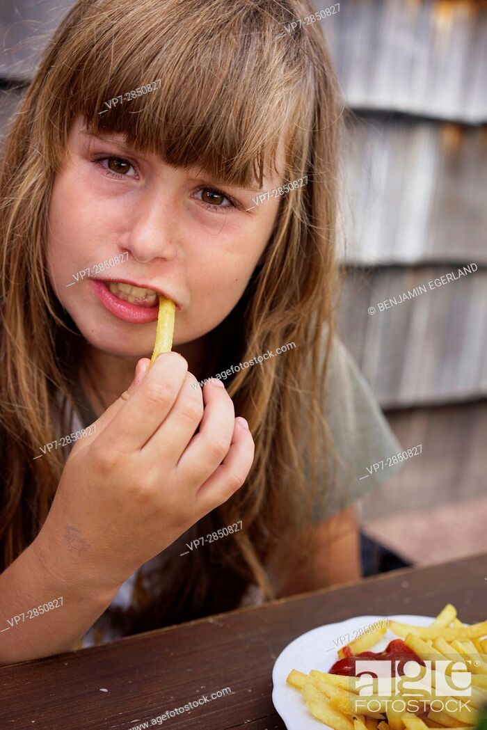 Stock Photo: young girl eating French Fries.