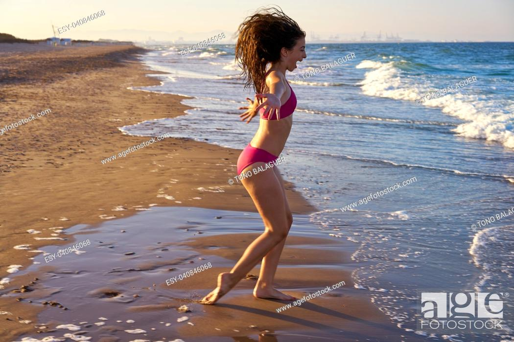 Stock Photo: Bikini girl running to the beach shore water of Mediterranean sea.